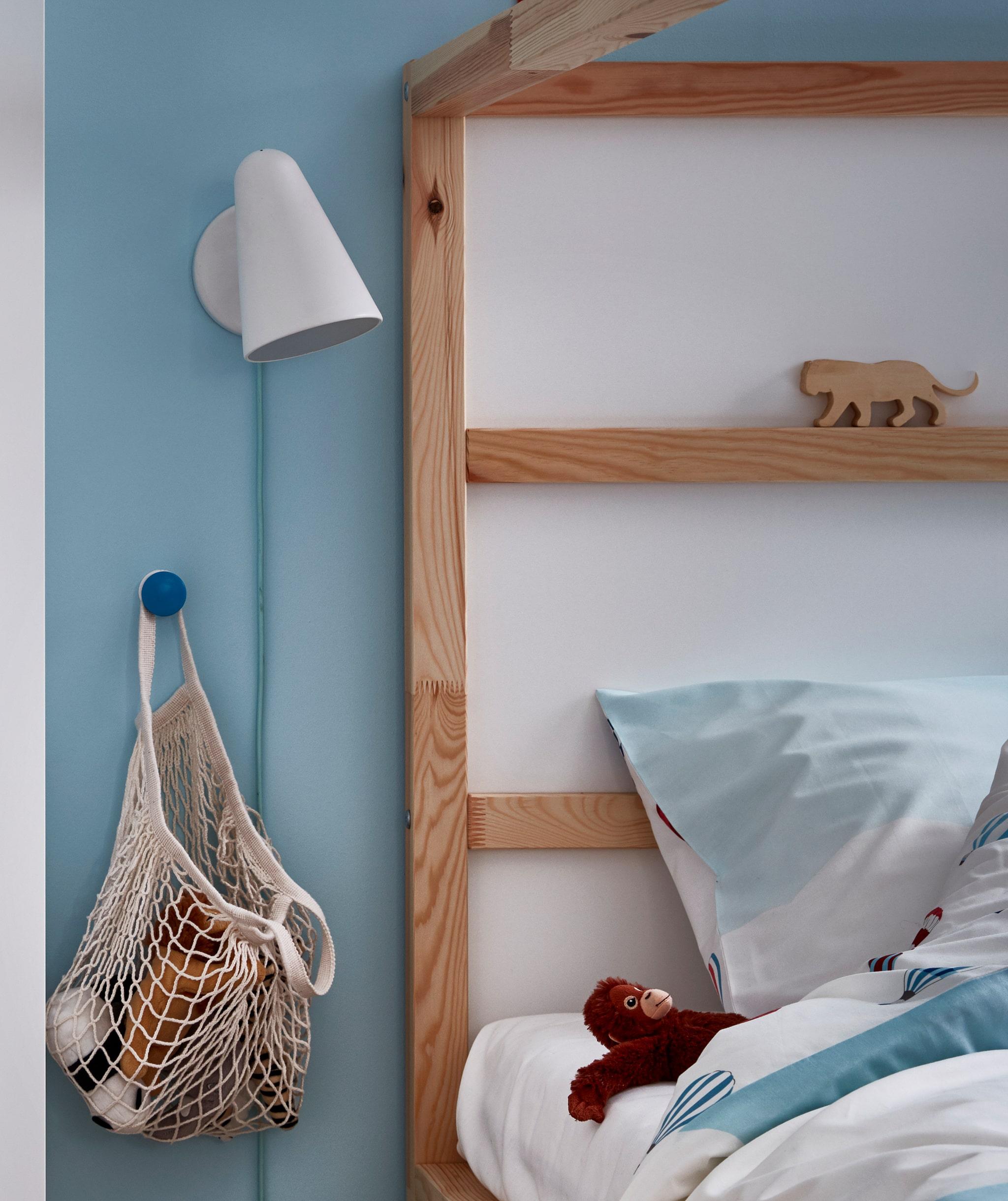 Ujung kepala tempat tidur anak-anak dengan sekantong boneka tergantung di samping tempat tidur. Lampu dinding, boneka berada di dekat bantal.
