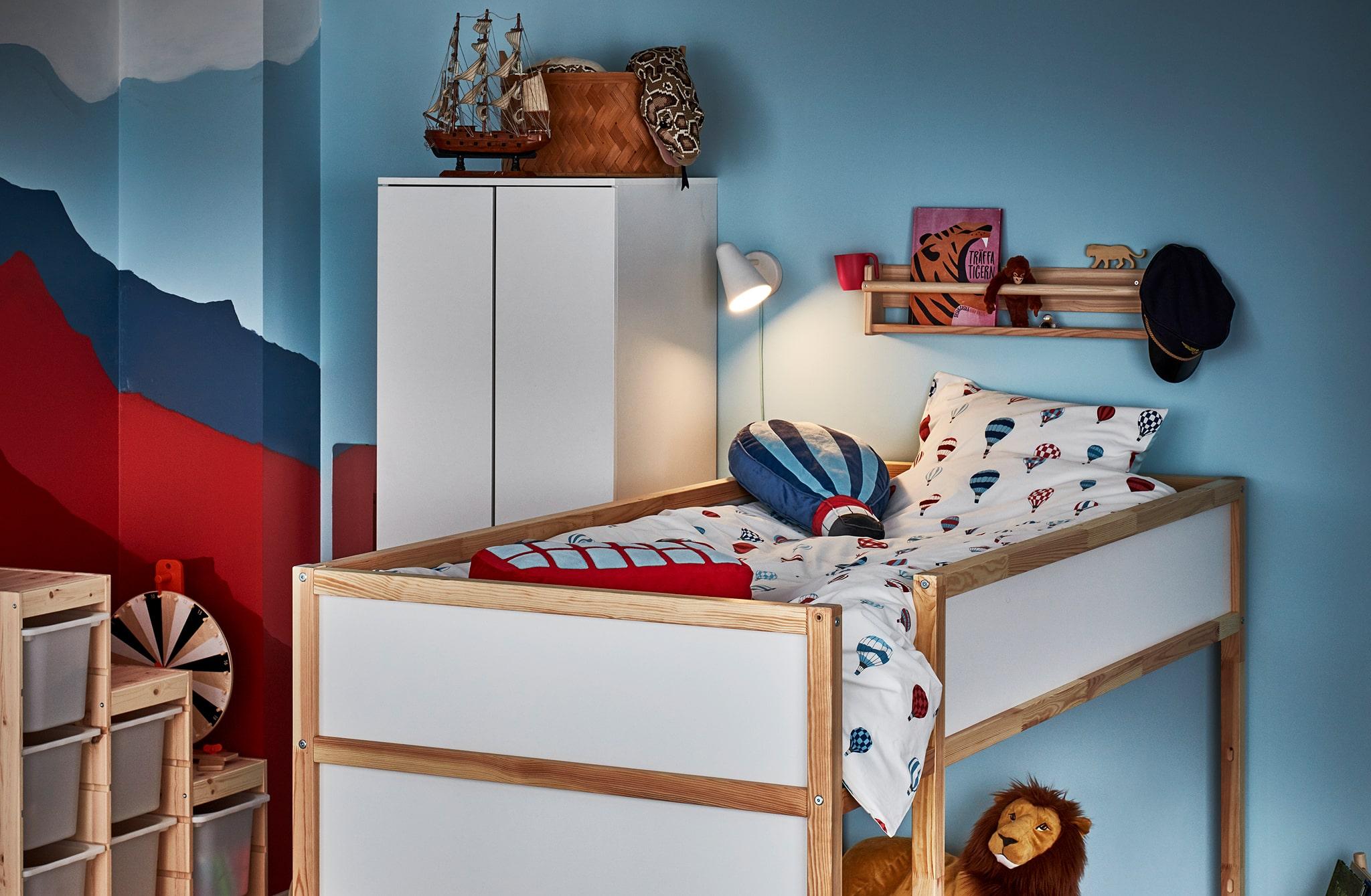 Sudut kamar anak dengan tempat tidur yang dapat dibalik dalam posisi matras di atas, ambalan rak dengan buku dan mainan, lampu tidur menyala.