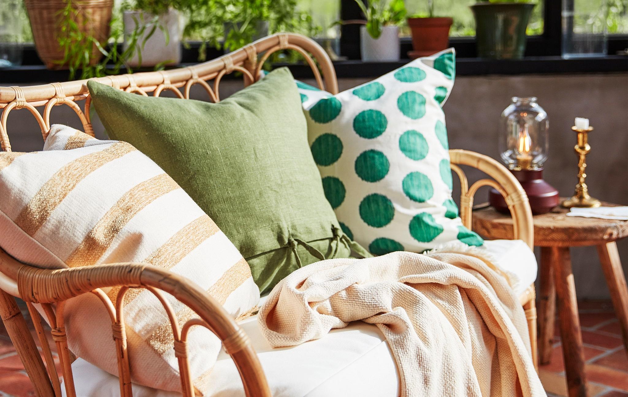 Tiga bantal dengan pola berbeda dalam warna teduh, diletakkan di sofa rotan di ruang tamu.
