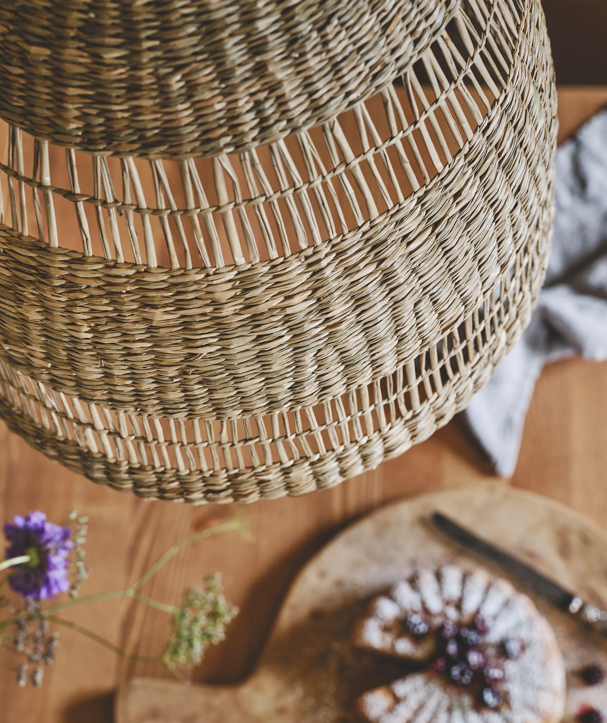 Tampilan dekat dari pola dekoratif lampu gantung yang terbuat dari lamun alami, tergantung di atas meja kayu.