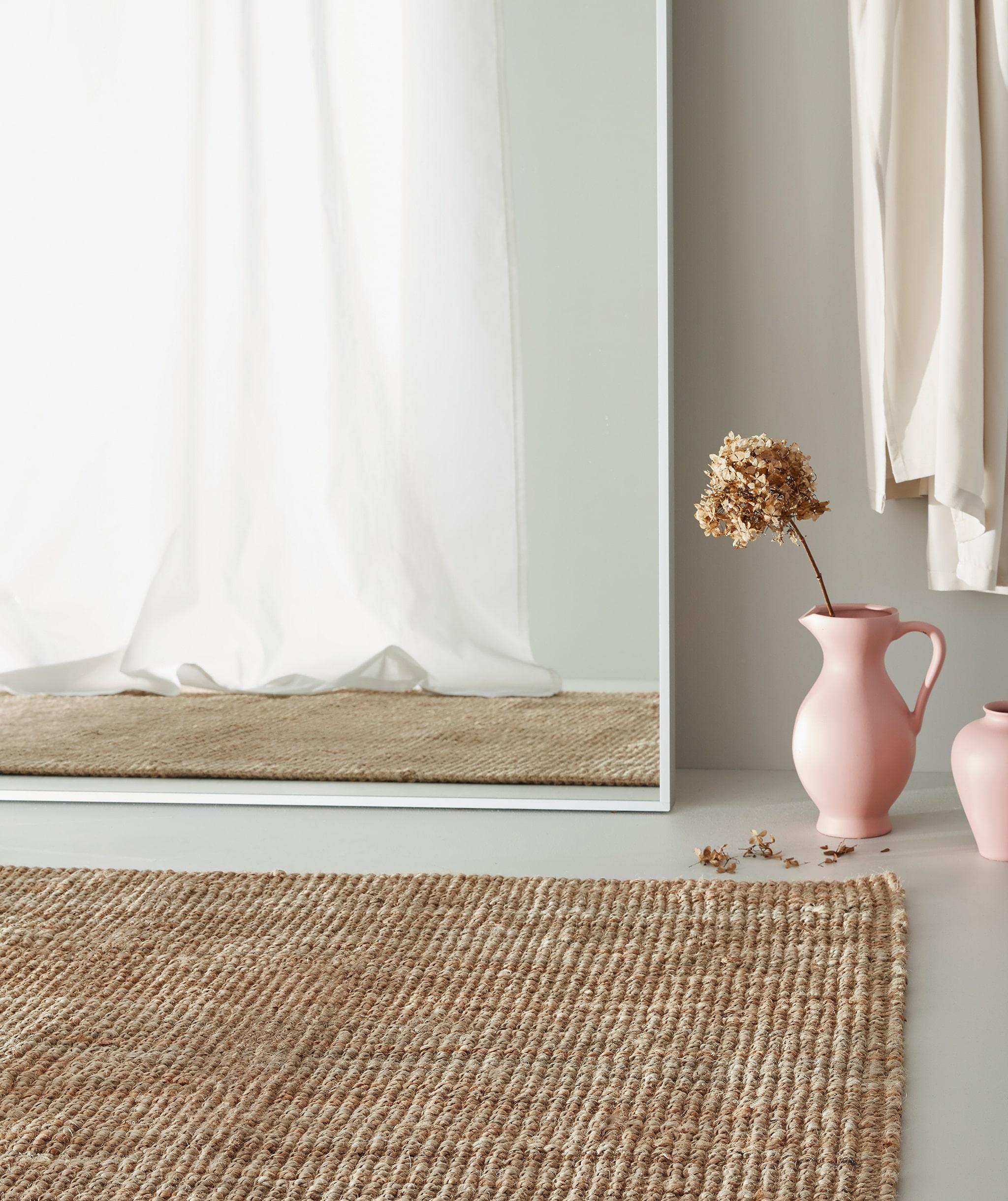 Karpet rami di lantai abu-abu, vas merah muda dengan bunga kering ada di sebelah cermin putih besar yang memantulkan tirai putih.