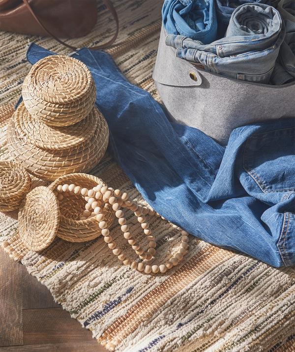 Tiga kotak bulat kecil dari bahan lamun alami, ditempatkan di sebelah beberapa pasang celana jins biru dan kotak penyimpanan abu-abu.