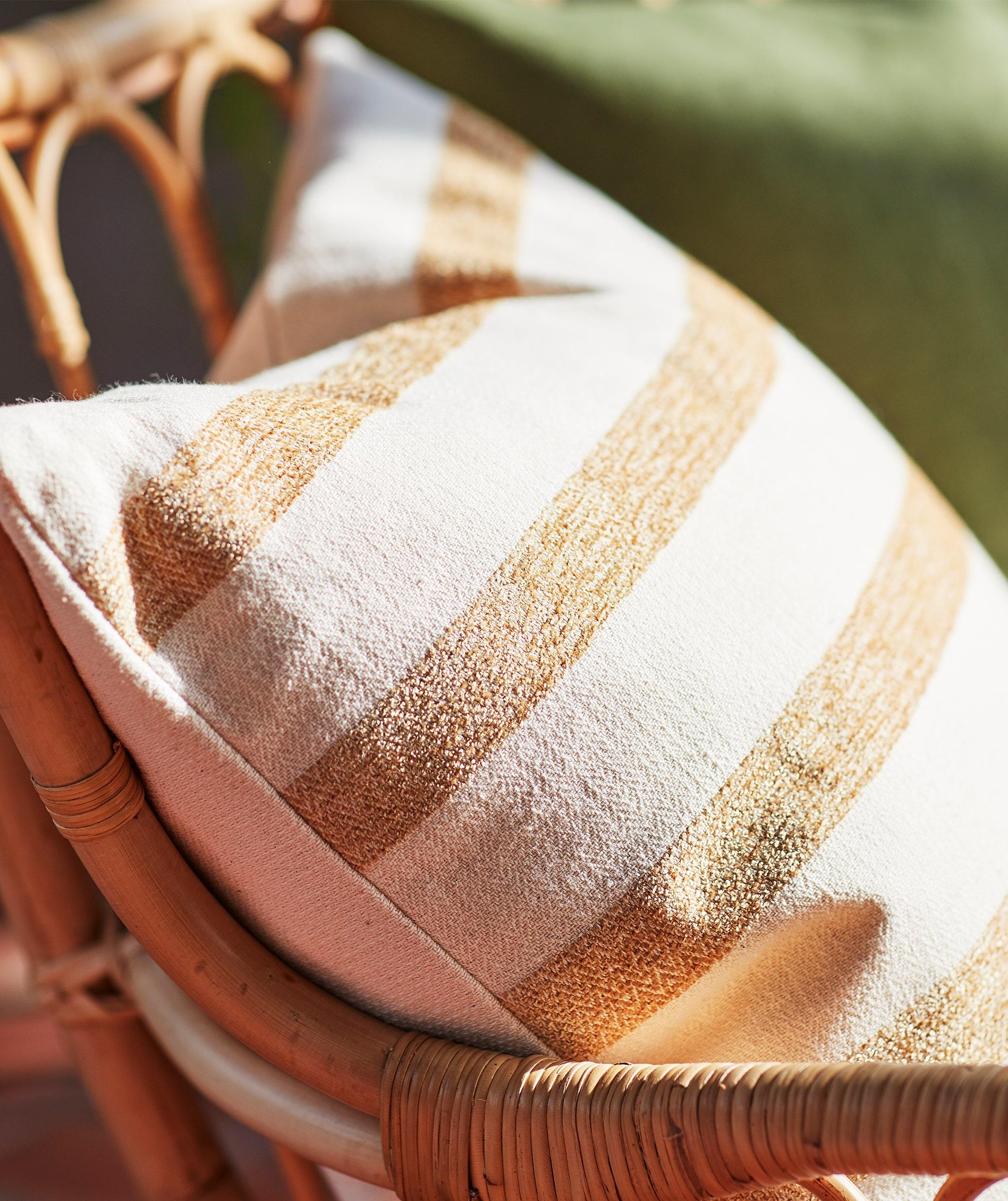 Tampilan bantal kapas bergaris-garis warna krem dan cokelat muda di kursi rotan.