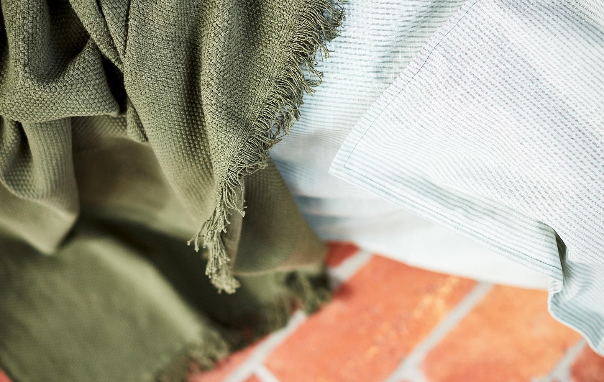 Tampilan dekat dari selimut warna hijau dan kain bergaris abu-abu muda, diletakkan di lantai batu warna merah.