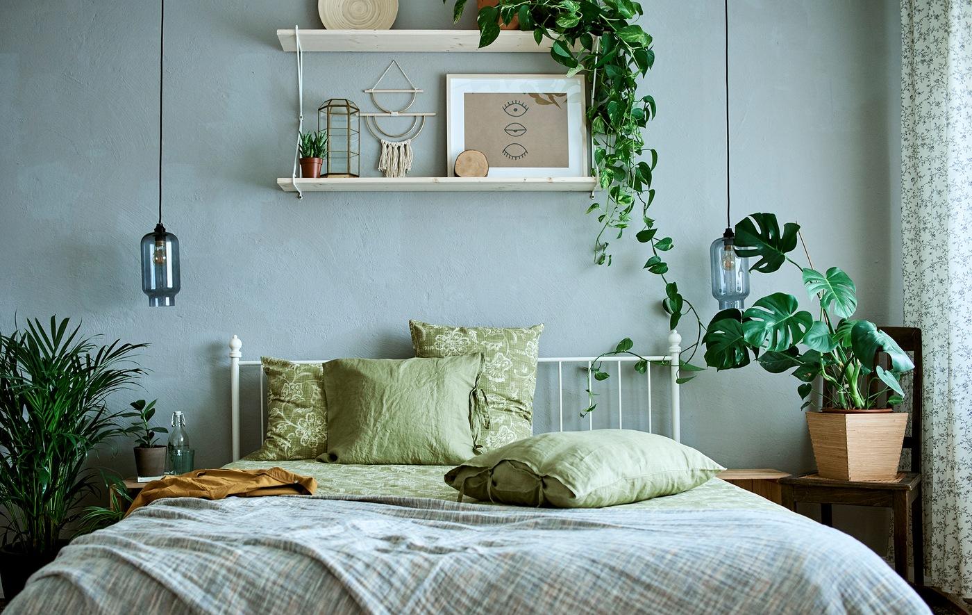 Rangka tempat tidur besi warna putih dengan seprai serta sarung bantal warna hijau polos dan bercorak di sebuah ruangan yang didekorasi tanaman dan karya seni.