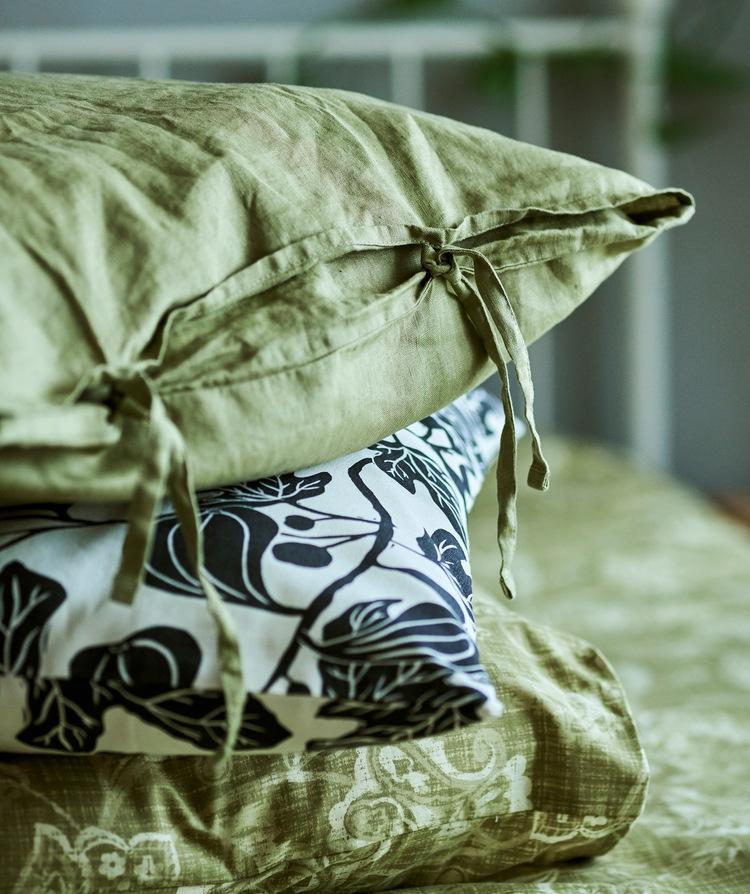 Tumpukan tiga bantal dengan sarung bantal yang berbeda-beda - linen hijau dengan tali, bercorak daun warna monokrom dan bercorak paisley warna hijau.