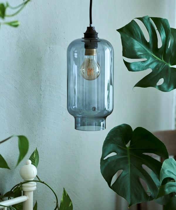Kap lampu gantung kaca berwarna biru tergantung di samping rangka tempat tidur putih, bersebelahan dengan tanaman MONSTERA.