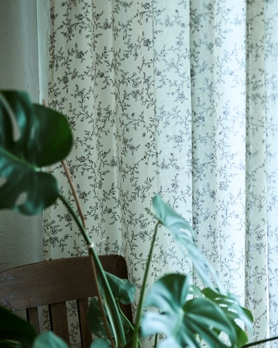 Tirai putih dengan corak tanaman warna hitam tergantung di jendela bersebelahan dengan kursi makan kayu gelap dan tanaman MONSTERA.