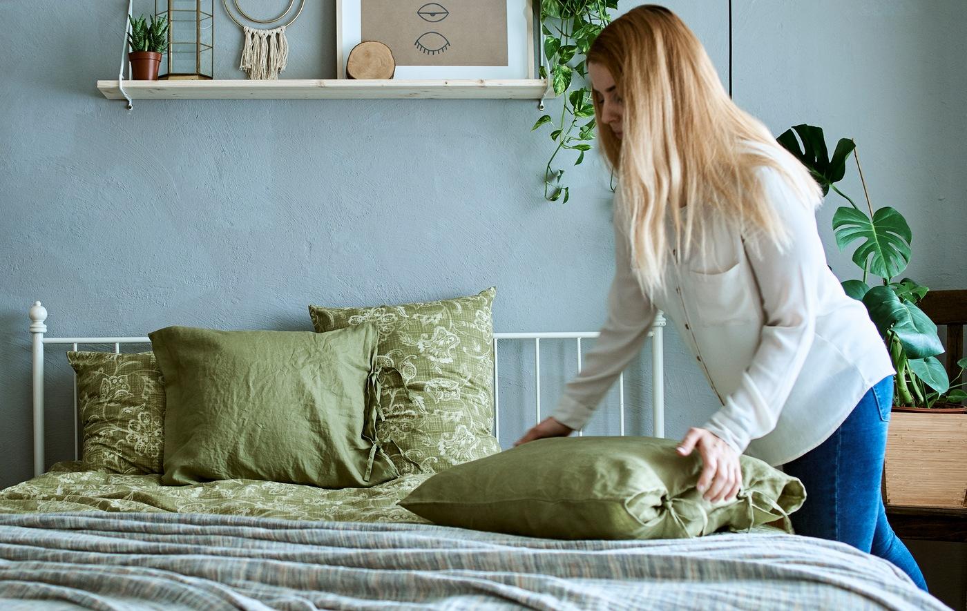 Seorang wanita di kamar tidur dengan nuansa abu-abu dan hijau, berisi tanaman, menepuk sebuah bantal di atas tempat tidur dengan sarung warna hijau.