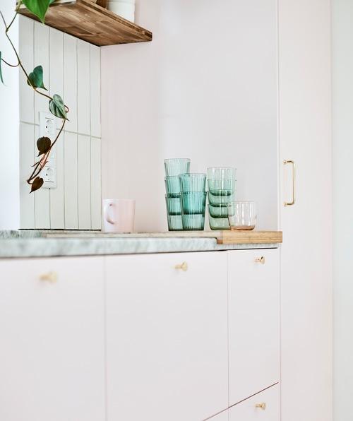 Deretan unit dapur dengan pintu merah muda dengan tumpukan gelas hijau dan sebuah mug merah muda di atas talenan di atas meja marmer.