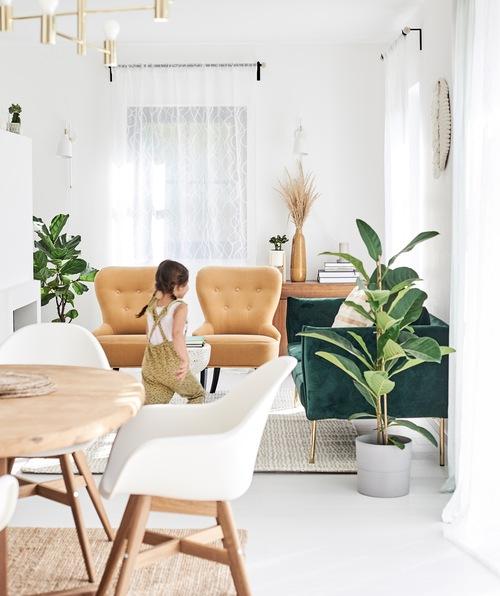 Seorang anak perempuan berlari melalui ruang makan / ruang tamu terbuka dengan sofa beludru hijau, kursi santai warna mustard dan kursi makan putih.