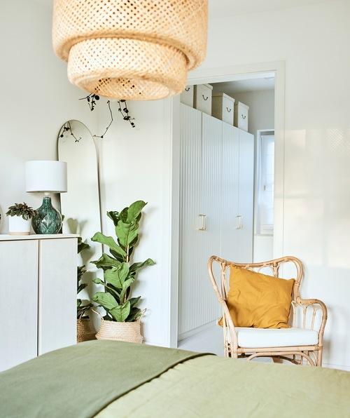Tempat tidur dengan linen hijau di sebuah kamar dengan kursi rotan dan lampu langit-langit anyaman dan sebuah ruang kecil dengan lemari pakaian warna putih.