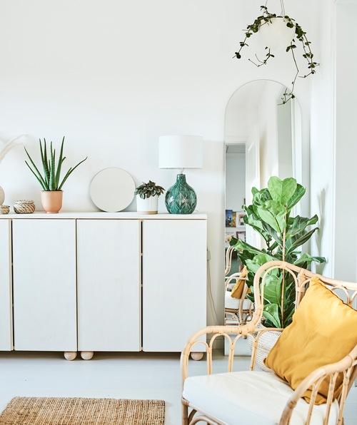 Lemari warna putih dengan tanaman, cermin dan lampu hijau di atasnya, cermin berbentuk lengkung dibingkai oleh tanaman gantung.