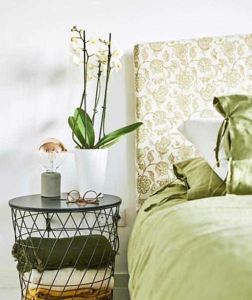 Seprai hijau di atas tempat tidur dengan sandaran kepala yang terbuat dari kain bermotif paisley hijau, kacamata dan bunga anggrek ada di meja samping tempat tidur.