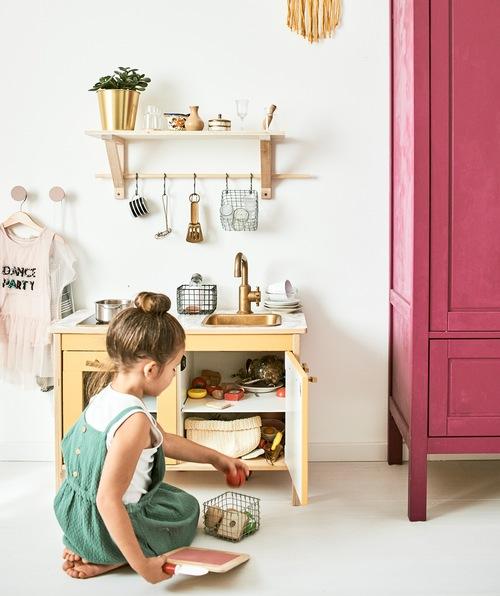 Seorang anak perempuan bermain dengan dapur mainan beserta perlengkapannya termasuk panci mainan, makanan dan peralatan masak yang tergantung di rak.