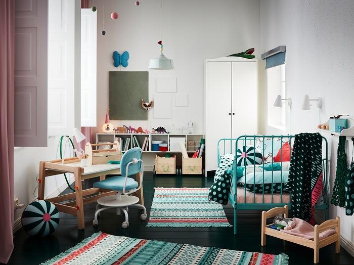Kamar anak-anak dengan karpet berwarna-warni, rangka tempat tidur berwarna toska, lemari pakaian berwarna putih, tirai berwarna merah muda, dan meja belajar anak.