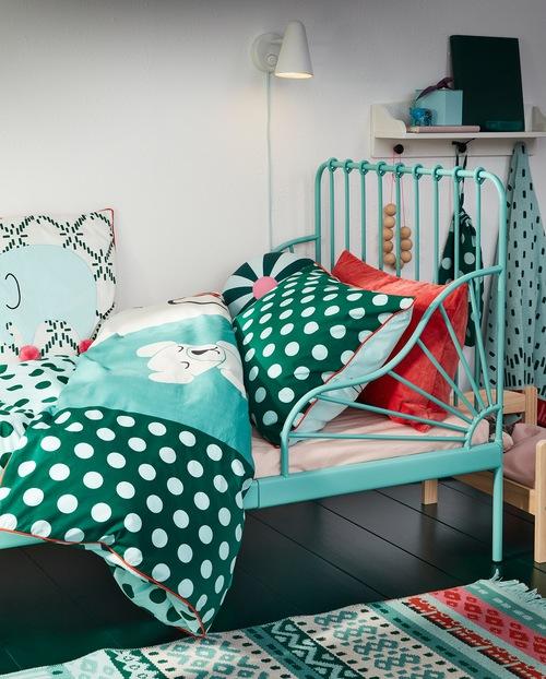 Rangka tempat tidur yang dapat diperpanjang berwarna toska dengan linen tempat tidur dengan motif tambal sulam / mainan berwarna toska, biru dan putih.