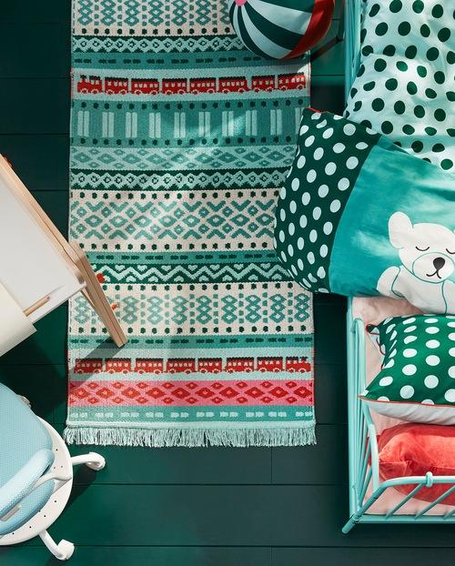 Mainan KÄPPHÄST, karpet tipis, dan linen tempat tidur dalam pola warna-warni – semua menciptakan tampilan yang terkoordinasi.