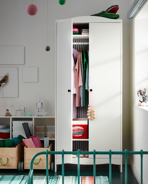 Kamar tidur anak dengan lemari pakaian yang salah satu pintunya terbuka. Kotak penyimpanan dan pakaian yang digantung dan dilipat disimpan di dalamnya.
