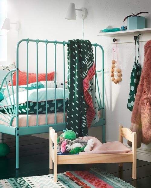 Tempat tidur boneka DUKTIG dengan material kayu solid pinus dengan sprei dan boneka terletak di sebelah tempat tidur anak berwarna toska.