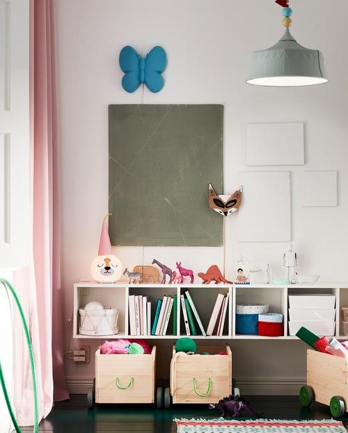 Unit rak penyimpanan berwarna putih terpasang di dinding. Mainan, buku, keranjang, dan lampu meja terletak di rak dan bagian atas.