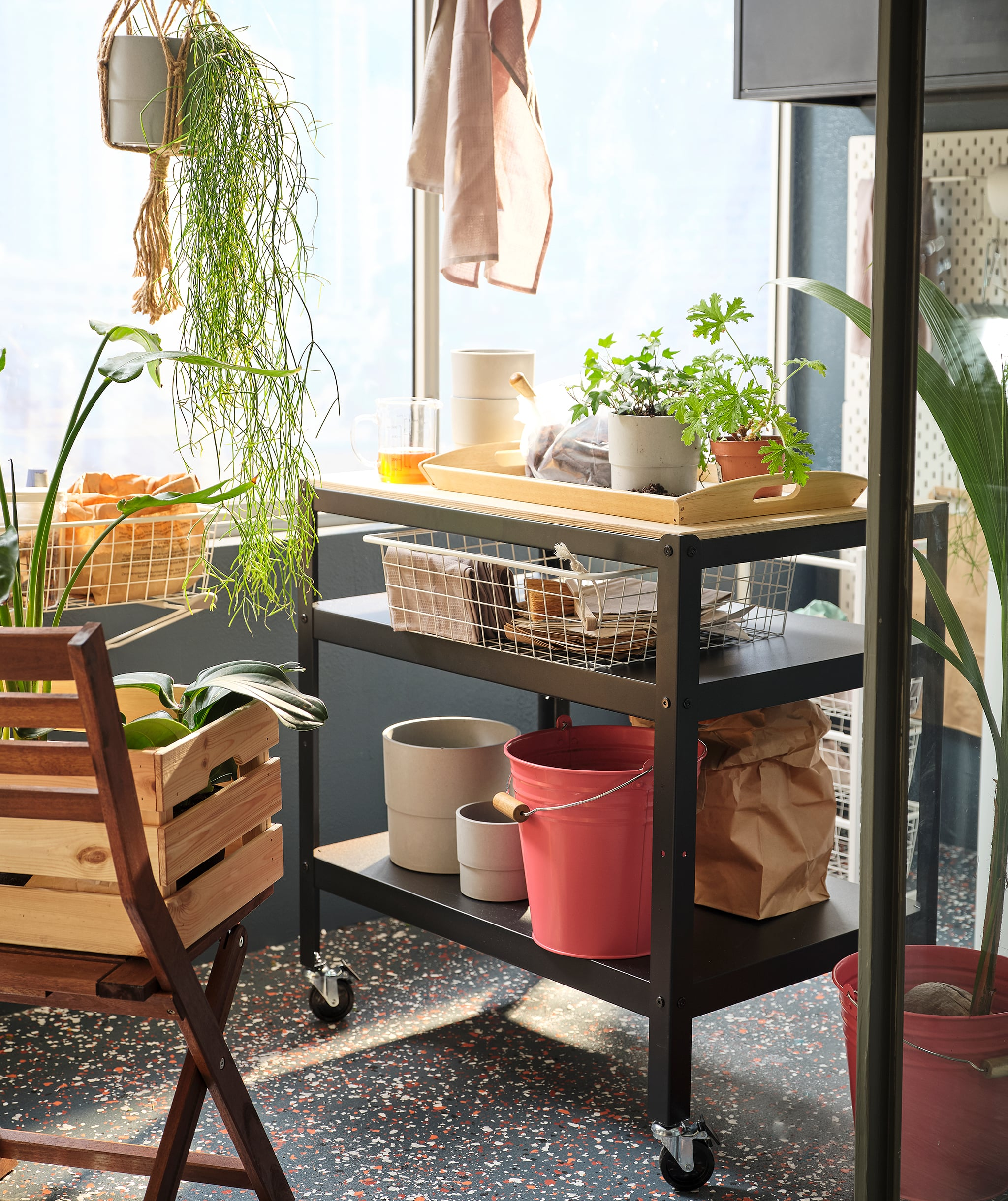 Balcony with a minute sideboard created by a chopping board placed on SKRÄLL hooks; tea and a plant pot on it, chairs beside.