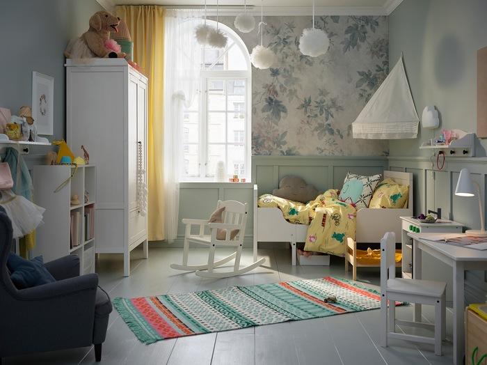 Kamar anak dengan ranjang, kanopi, lemari, meja dan kursi berwarna putih. Karpet warna-warni terletak menutupi lantai.