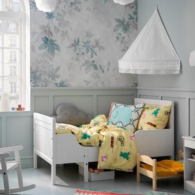 Rangka ranjang SUNDVIK yang dapat diperpanjang berwarna putih dengan linen tempat tidur berwarna kuning. Kanopi tempat tidur dipasang di dinding tergantung di atasnya untuk memberikan nuansa nyaman.