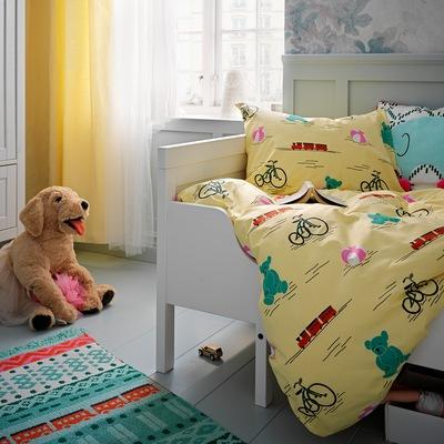 Sprei Kuning KÄPPHÄST bermotif mainan  di tempat tidur anak berwarna putih. Karpet berwarna-warni dan boneka anjing di lantai di sebelahnya.