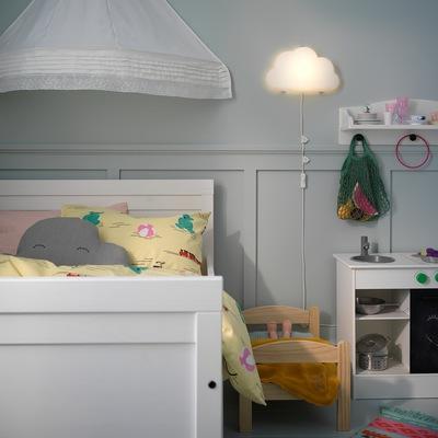 Lampu LED dinding UPPLYST yang dipasang di dinding  berbentuk seperti awan dan memberikan cahaya yang nyaman di sebelah tempat tidur anak berwarna putih.