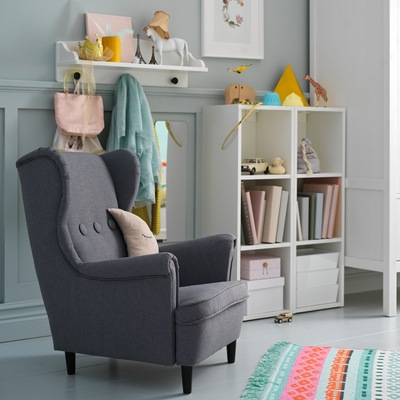 Kursi berlengan anak-anak STRANDMON berwarna abu-abu gelap terletak di sebelah unit rak penyimpanan berwarna putih yang menyimpan buku dan mainan.