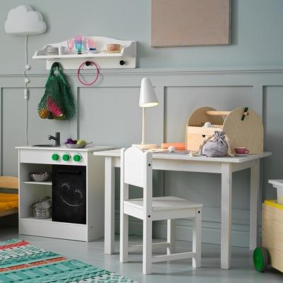 Kursi anak-anak dan meja belajar anak-anak dengan lampu meja dan kerajinan tangan di atasnya, dan terletak di sebelah dapur bermain berwarna putih.