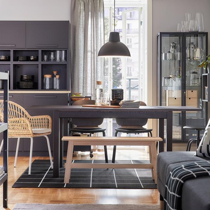 Ruang makan dengan meja yang dapat diperpanjang. Kursi berwarna hitam, kursi dengan material rotan, dan bangku dengan material kayu birch yang menyediakan tempat duduk ekstra.