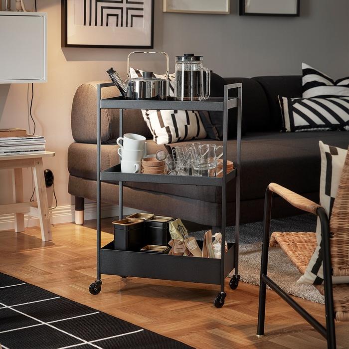 Troli NISSAFORS berwarna hitam dengan teko, mug, dan kantong teh di raknya berada di samping sofa dan kursi berlengan.