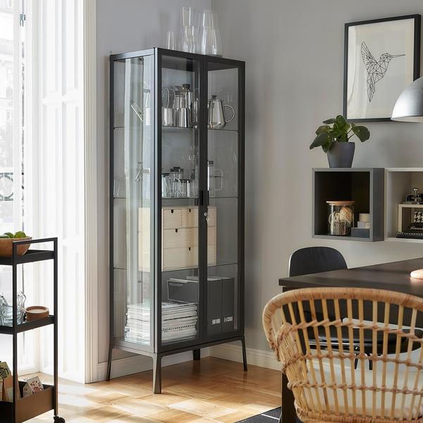 Kabinet pintu kaca MILSBO berdiri di sebelah pintu balkon. Barang-barang dekoratif, majalah dan file majalah disimpan di dalamnya.