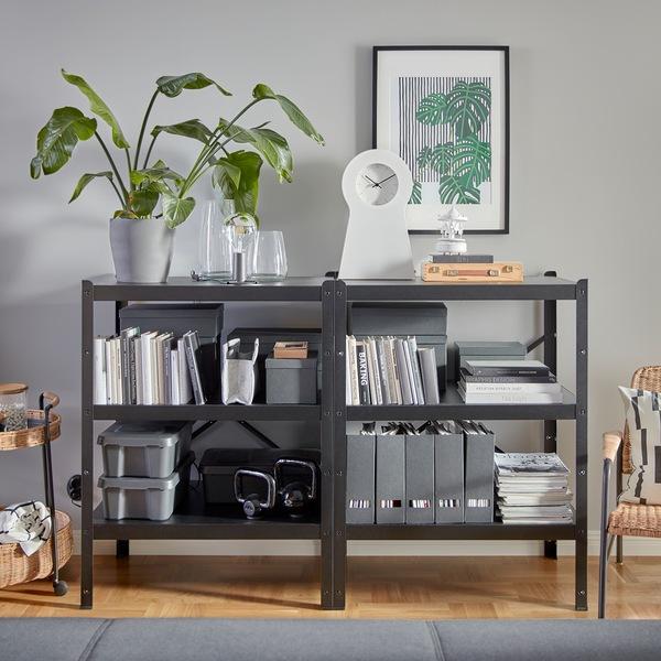 Dua unit rak BROR hitam dan kokoh yang menampung banyak barang dekoratif, buku, file majalah, kettlebell dan banyak lagi.