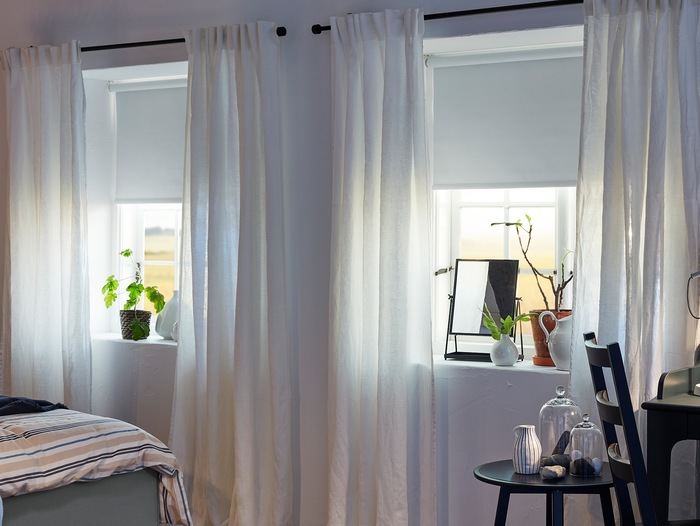 AINA curtains in white are hanging on black curtain rods in two bedroom windows where also white roller blinds are mounted.