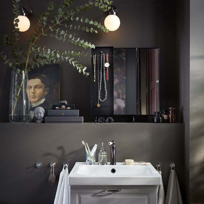 A black mirror, a vase with eucalyptus, two round wall-mounted lamps and a white wash-basin.