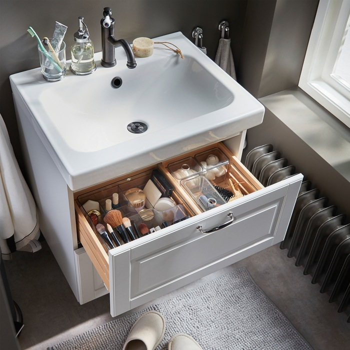 Makeup, hair tools and beauty tools are nicely organised in smoke-coloured see-through boxes that are in a wash stand drawer.