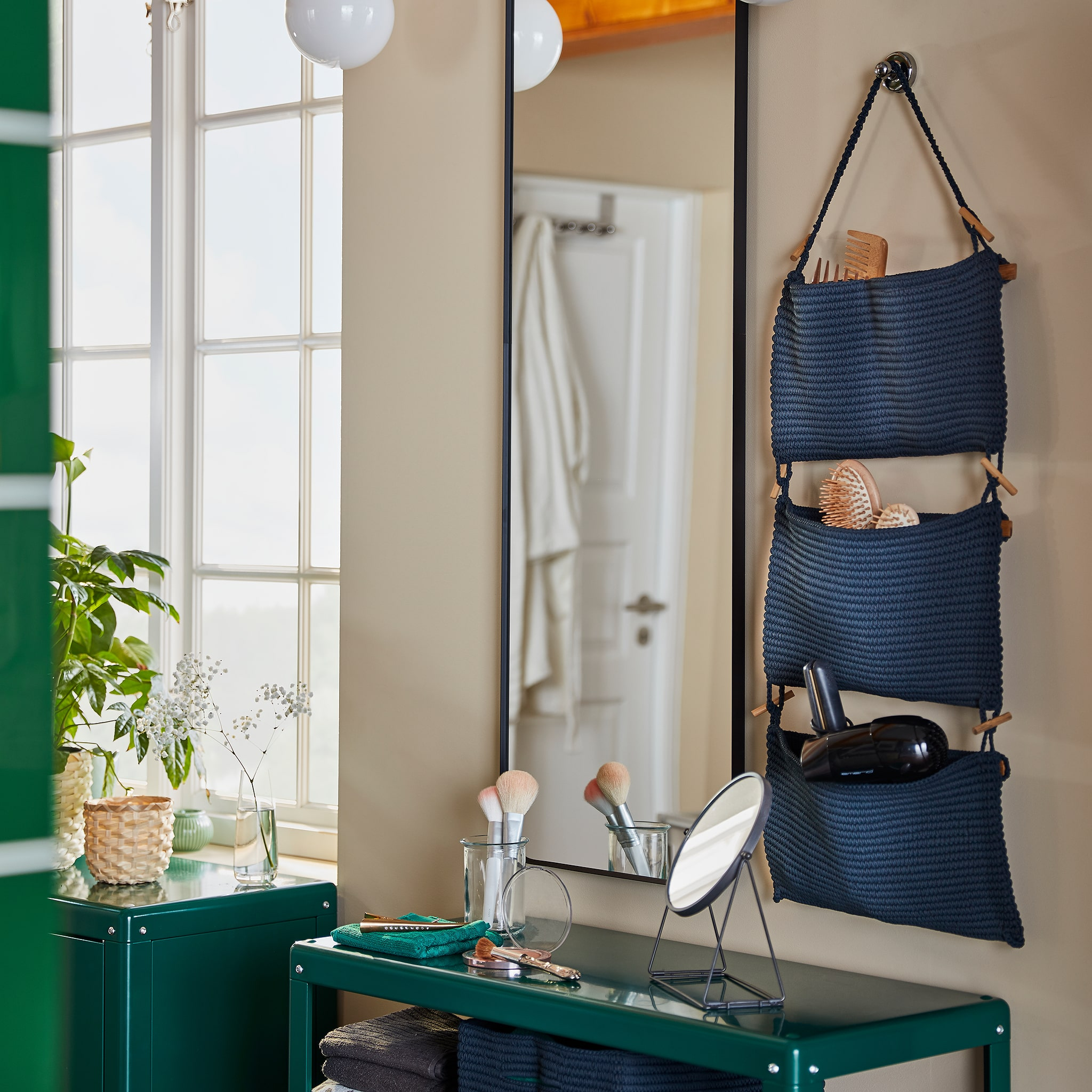 A bathroom beauty station that consists of NORDRANA hanging storage, a wall-mounted mirror and a green shelving unit.