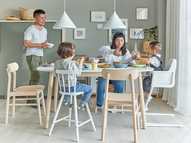 Keluarga sedang berada di ruang makan. Ibu dan dua anak duduk di samping meja makan, dan sang ayah membawa mangkuk ke meja.