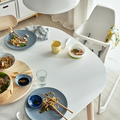 Meja makan berwarna putih dengan sisa makanan dari acara makan malam keluarga. Di sebelah meja terdapat kursi tinggi berwarna putih.