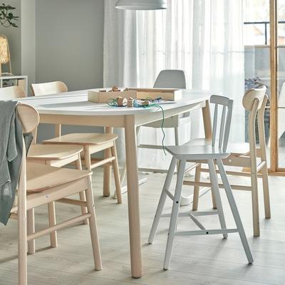 Meja makan, kursi dengan material kayu birch, kursi tinggi, dan kursi makan anak dengan penyangga kaki. Kerajinan tangan anak-anak terletak di atas meja.