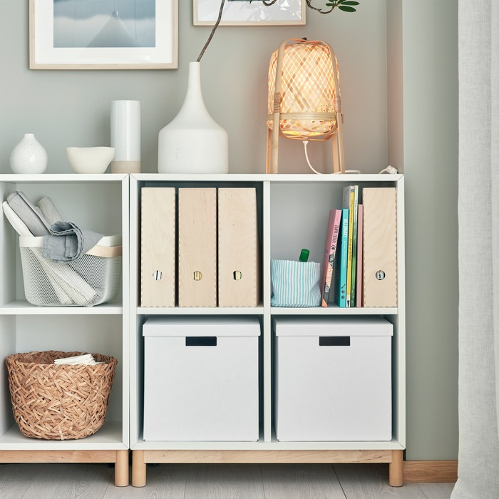 Kombinasi kabinet penyimpanan EKET putih dengan kaki bermaterial kayu birch. Kotak penyimpanan dan dekorasi yang berbeda berada di rak dan di bagian atasnya.