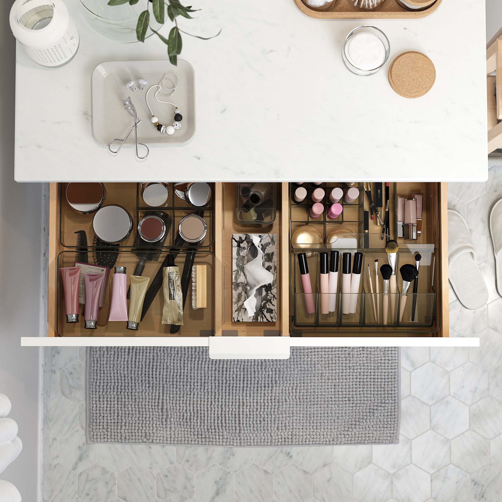 A wash-stand with a countertop in a marble effect. A drawer is open and inside are GODMORGON boxes that help organise makeup.