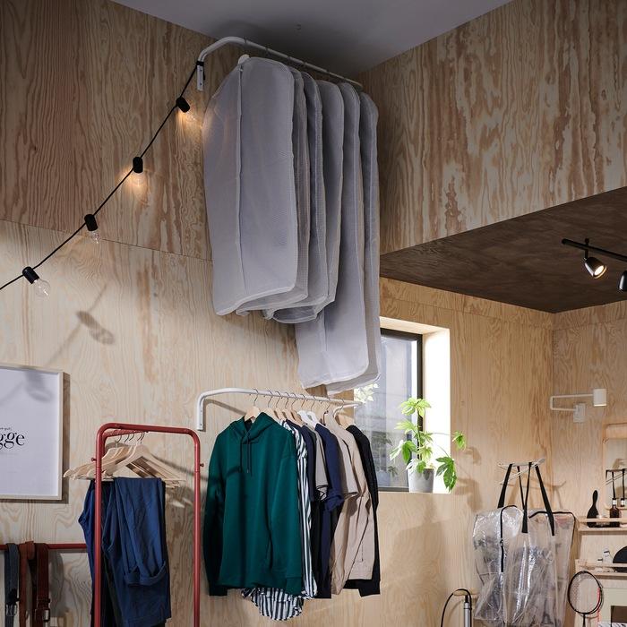 Dua batang gantungan pakaian dipasang di dinding. Salah satunya adalah di plafon dan menyimpan pakaian dalam kotak penyimpanan, dan satunya dipasang lebih rendah dan mudah dijangkau.