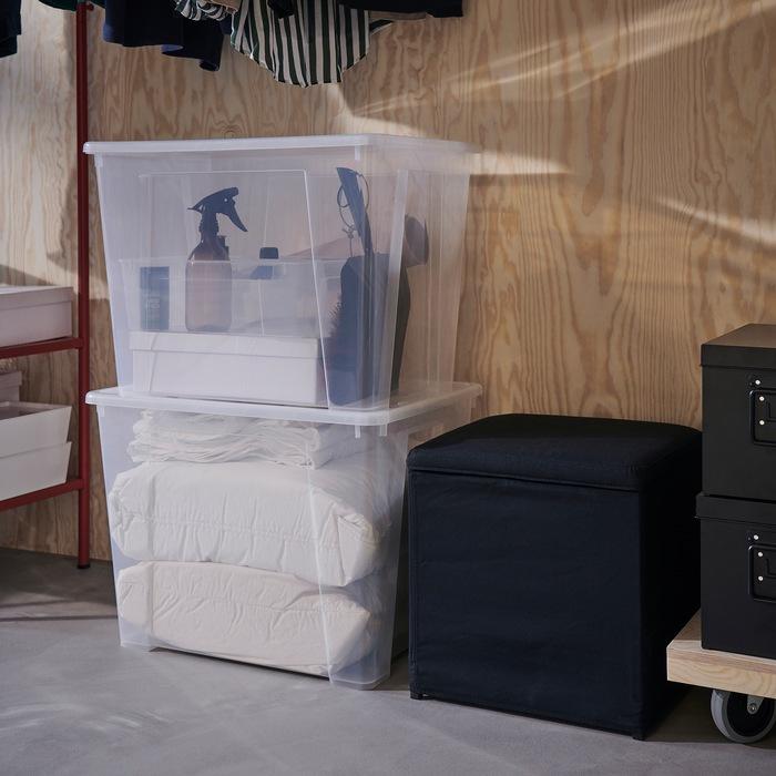 Dua kotak penyimpanan SAMLA transparan ditumpuk di lantai, di sebelahnya ada bangku hitam dengan penyimpanan di dalamnya.