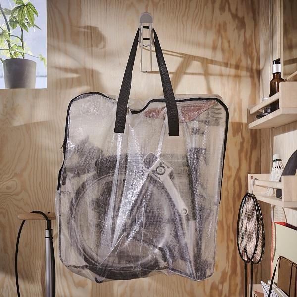 Tas penyimpanan DIMPA yang transparan dengan sepeda lipat di dalamnya, tergantung di pengait yang dipasang di dinding kayu.