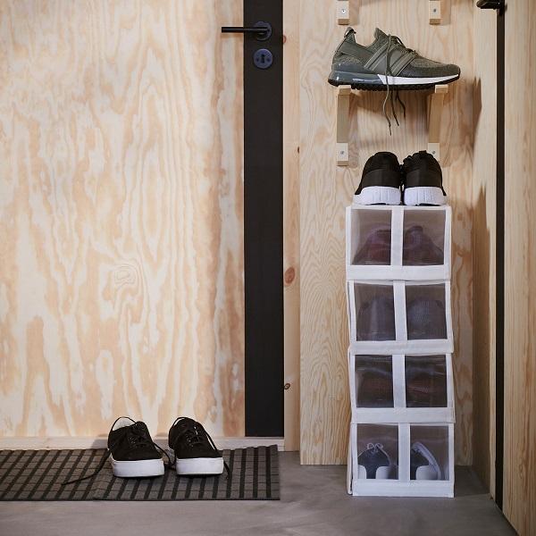 Kotak sepatu sempit berwarna putih ditumpuk di dinding sempit di sebelah pintu. Di atas kotak penyimpanan terdapat braket yang menyimpan lebih banyak lagi sepatu.