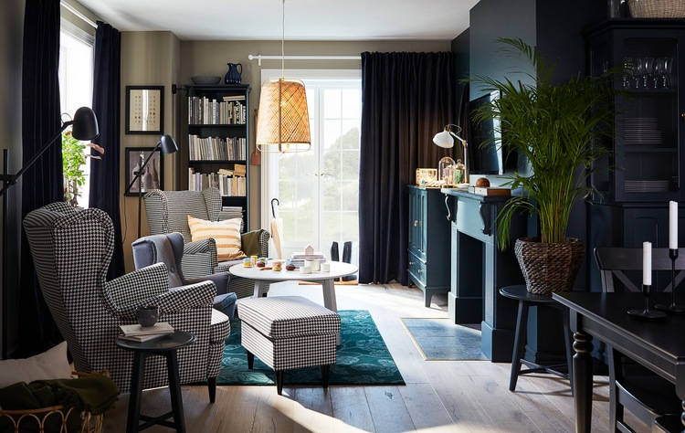 Ruang tamu dengan dua kursi berlengan yang bermotif houndstooth, karpet berwarna hijau, lampu gantung dengan material bambu, dan meja tamu berbentuk bulat.